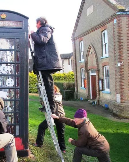The phone box was given a lick of grey paint before it is painted red again in the summer.