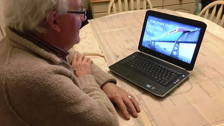John Davis watching the video of the Train that Floats in the Sky. He worked as a graphic designer a