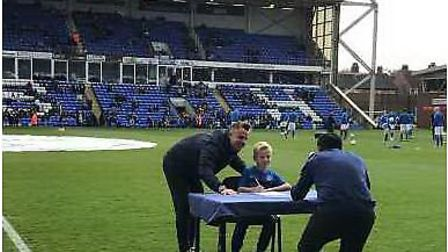 March footballer Ashton Newton signs his contract for Peterborough United at the club's ABAX Stadium