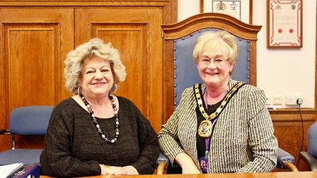 Fenland District Council's new chairman, Cllr Kay Mayor (right), receives the chain of office from o