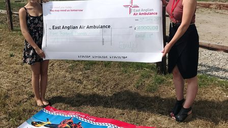 Emily James presents her cheque to Fern Clark from the East Anglian Air Ambulance.