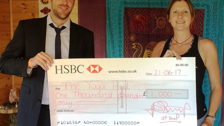 Jon Stump presenting the £1,000 cheque to Sally Talbot, owner of The Yoga Hut.