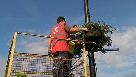 Workers hanging the group's floral displays in Chatteris.