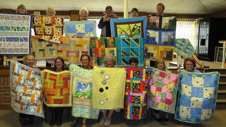 The Elysian Quilters show off their 22 hand-stitched quilts which they will donate to EACH.