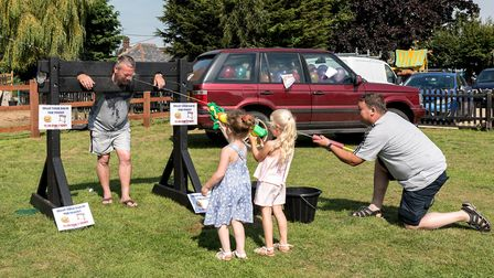 This sporting stall-holder was invited into the stocks just so the children had someone to squirt at