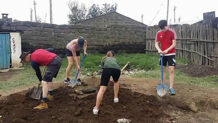 Ely College students digging in the grounds of one of the school's they helped in Kenya as part of t
