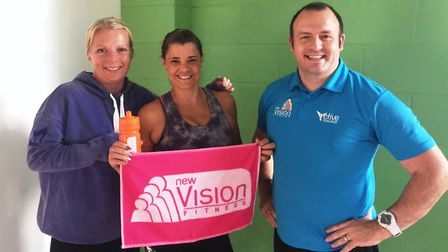 Clair Kirby (centre) shows off her other prizes, a water bottle and towel, with New Vision Fitness i