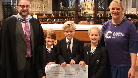 Fundraisers at King's Ely Junior raised almost £18,000 for Cancer Research UK and presented the cheq