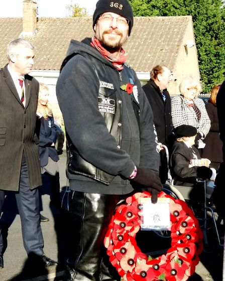 Mark Robinson, president of the Littleport 363MCC Motorcycle Club, preparing to lay a poppy wreath.