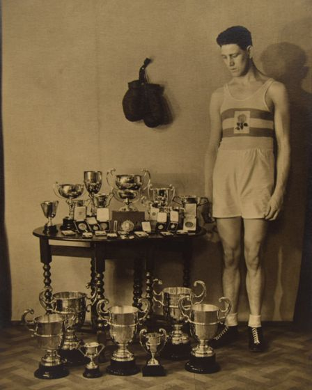 Hugh Pat Floyd, British champion boxer, with a selection of trophies. The picture is going under the