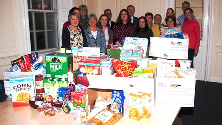 Cathy Wright from Ely Foodbank (third from left) with staff at Ward Gethin Archer with their donatio