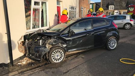 Two people were taken to hospital with injuries after a car crashed into a house on the A605 at Whit