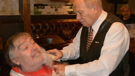 Ely artist Ian McKendrick having his 'Santa beard' shaved off for charity by Tony from Milan Barbers