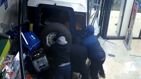 Three masked men can be seen trying to secure the cash machine to the back of the Land Rover