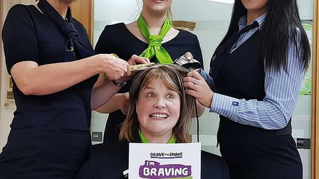 Tracy Harley (front) prepares to have her head shaved with colleagues (l-r) Nicola Roberts, Ellie Jo