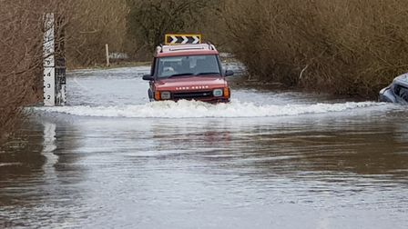 Cars attempting to use the A1101 in Welney despite flood warnings, one car is seen half submerged in