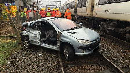 A train has hit a car at a level crossing, causing delays to rail services between Norwich and Cambr