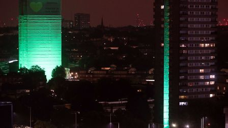 Grenfell Tower (left) in west London is illuminated in green along with its surrounding towers to ma