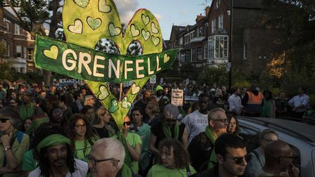 People take part in a silent walk by Grenfell Tower, to mark one year since the blaze which claimed