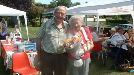 Enid and John Bedford receiving a bouquet from Ely Rotary Club