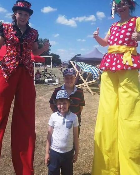 Joker Entertainment stilt walkers with Louis and Ethan at Wimblington fun day. PHOTO: Joanne Rose.