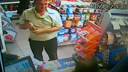 The moment a man threatens shop worker with hammer in Earith armed robbery. Photo: Cambs Police