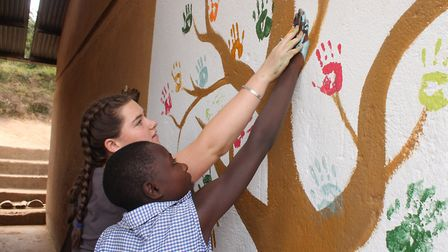 A Felsted pupil and a Great Lakes High School pupil leave their hand prints on the side of a school