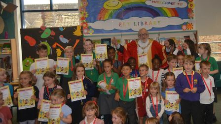 Mayor of Ely Mike Rouse pictured with children at Ely Library after being presented with Summer Read