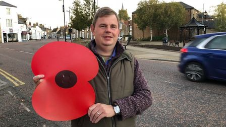 Chatteris Mayor Councillor James Carney iwth one of the giant poppies decorating the town.