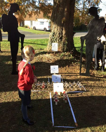 Florence Wright, five, looks at the crosses placed by her and other Rayne Primary & Nursary School p