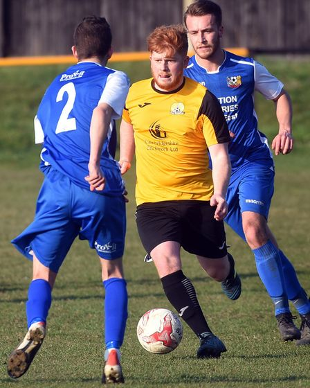 March Town man Lewis Gibson finds himself surrounded against Cornard. Picture: IAN CARTER
