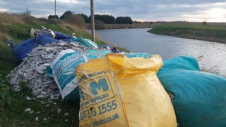Twelve bags of asbestos are dumped at the bottom of the Sixteen Foot Bank where the river joins the