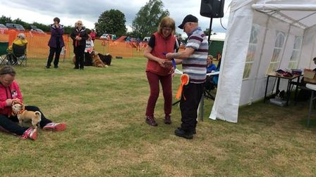 Pauline and her dog Ernie accepting her second place rosette from judge Tony Ryman for agility.
