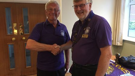 Outgoing March Lions Club president, Trevor Stockbridge, hands over his chain of office to the club'