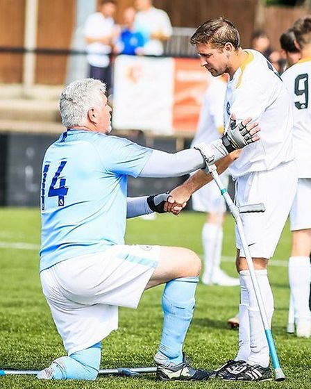 A Peterborough United Amputees player helps up his Manchester City compatriot after the final. Pictu