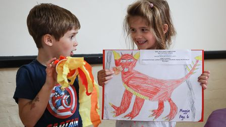 Maggie Christensen, age 6, with her winning dragon picture and brother Oscar, 5, looks on in amazeme