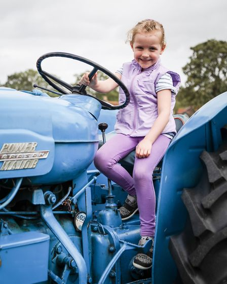 Francesca, 4, in the driving seat of a vintage tractor. Picture: CELIA BARTLETT PHOTOGRAPHY
