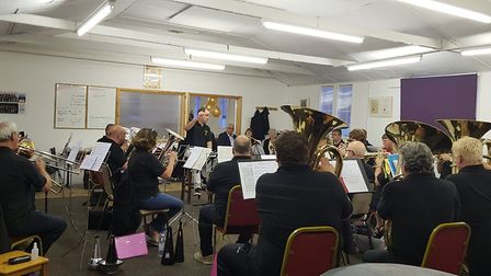 Musical director Ian Knapton puts the Littleport Brass Band through their paces in front of their si
