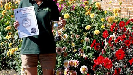 Volunteer Sam Baines with her certificate and cup in front of her award-winning display of dahlias.