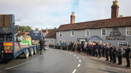 The low loader carrying Brian Law passes by the family and friends waiting at the side of the road