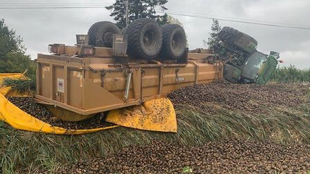 A tractor and trailer - with a full load of potatoes - overturned on the A1101 at Littleport today.