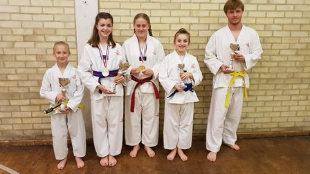 Mark Farnham Tae Kwon-Do members face the camera with trophies won at the TAGB British Championships