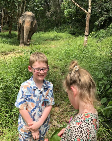 Oakley and his sister Daisy-Mai on holiday with one of the elephants