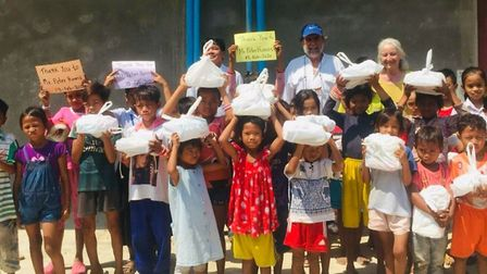 Peter with children from the CCH who hold bags of books. Picture: LIZ SAYERS
