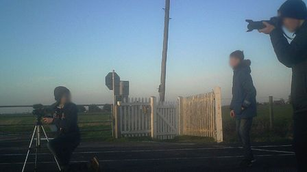 Three young boys have been spotted risking their lives as they take photos at Middle Drove level cro