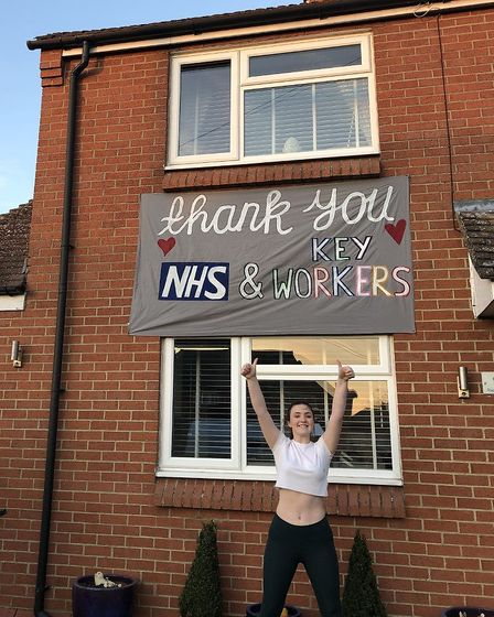 Ella Stock with her banner in support of keyworkers and NHS staff