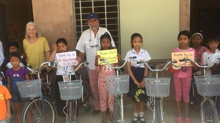 Peter Harris and Liz Sayers with some of the children who are able to go to school, thanks to their
