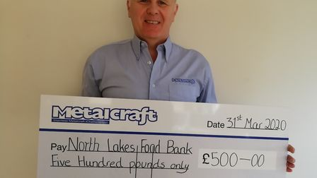 Stephen Buttriss, sales manager at Metalcraft, holds a cheque for £500 to North Lakes Food Bank. Pic