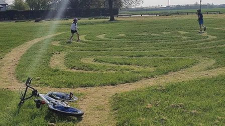 Children run around the labyrinth that Jane Frost has created. Picture: JENI GOWLER