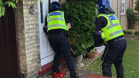Weapons including knives and a knuckle duster as well as £14,000 in cas were seized when police raid